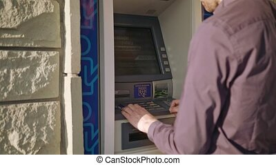 Young Man using ATM - A young man using an ATM. Close-up...