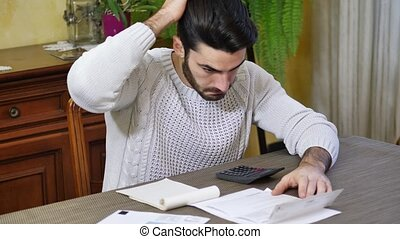 Young man using calculator and accounting at table.