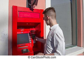 Young man using cash machine