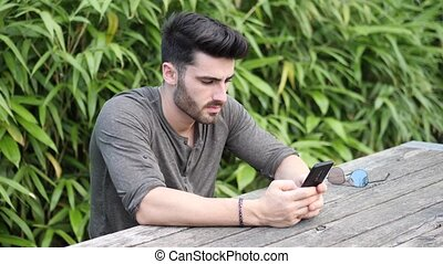 Young man using cell phone sitting on bench