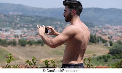 Young man using cell phone to film landscape - Young...
