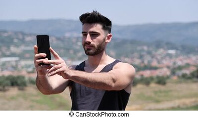 Young man using cell phone to send message - Young handsome...