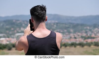 Young man using cell phone to take photos of landscape -...