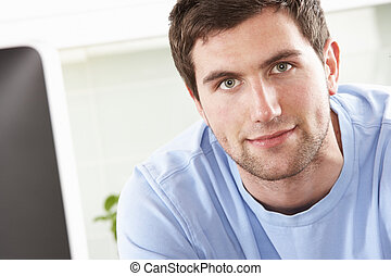 Young Man Using Computer In Modern Kitchen