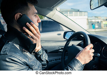 Young man using his phone while driving the car. Dangerous driving