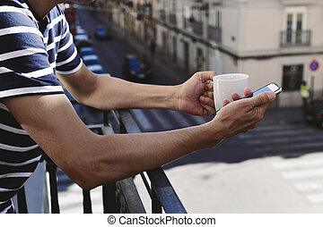 young man using his smartphone in the balcony