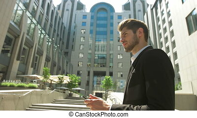 Young man using his tablet in front of a business center.