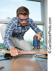 Young man using jigsaw on laminate flooring
