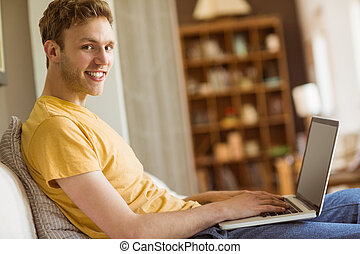 Young man using laptop on his couch