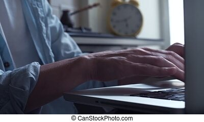 Young man using laptop pouring steaming coffee into a cupat kitchen.