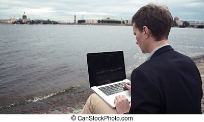 Young man using laptop sitting on bench near seafront. Summer day