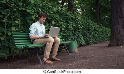 Young man using laptop with headphones sitting on bench at city park. Summer day