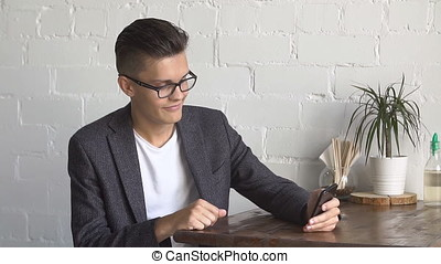 Young Man using Mobile Phone at Cozy Coffee Shop. - Young...