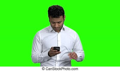 Young man using mobile phone on green screen. Handsome indian guy taking selfie with smartphone. Alpha Channel background.