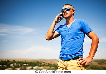 Young man using mobile smart phone, summer outdoor