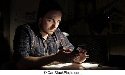 Young man using smartphone in cafe in the night