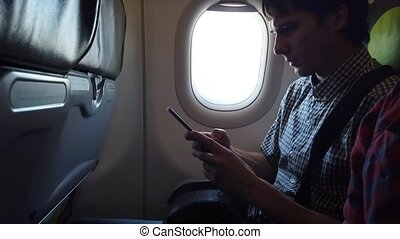 Young man using smartphone in the airplane.