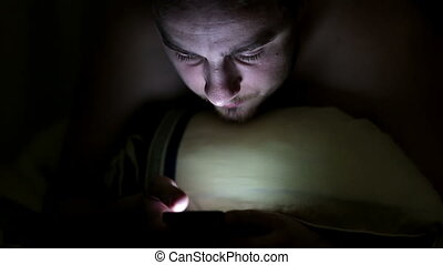 Young man using smartphone in the bed under blanket by night