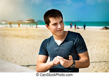 Young man using smartphone sitting on the city beach
