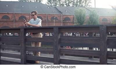 Young man using smartphone standing on a wooden bridge. City park at background.