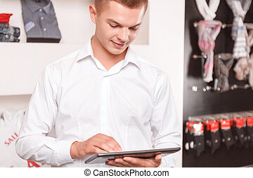 Young man using tablet at boutique