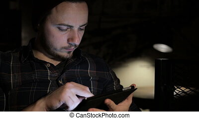 Young man using tablet computer in cafe in the night