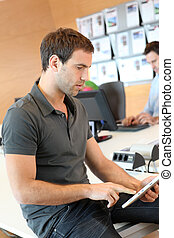 Young man using tablet in office