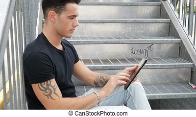 Young man using tablet PC outdoor in city