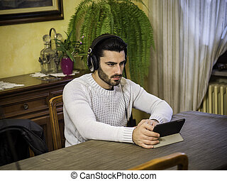 Young man using tablet PC to watch video or movie