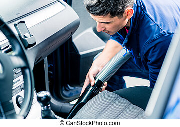 Young man using vacuum for cleaning the interior of a car