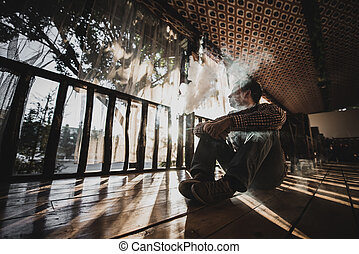 Young Man Using Vapourizer As Smoking Alternative