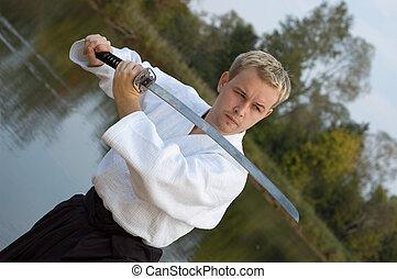 Young man v katana outdoors
