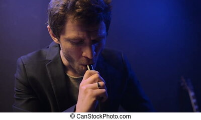 young man vaping with an electronic cigarette and make some smoke clouds