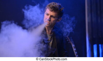 young man vaping with an electronic cigarette and make some...