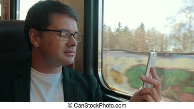 Young man video chatting on cell in train