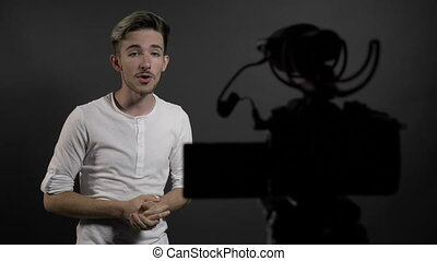 Young man vlog influencer talking to camera in home studio...