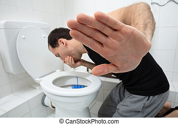 Young Man Vomiting In Toilet Bowl