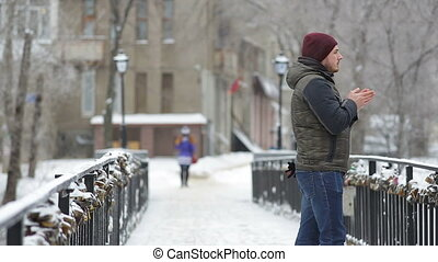 Young man waiting for someone in the winter city