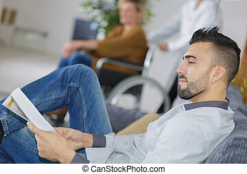young man waiting for the doctor in hospital lobby