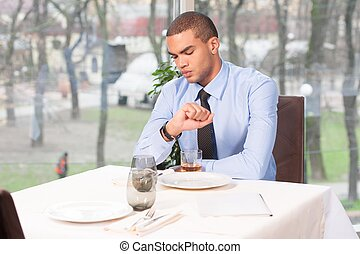 young man waiting for woman in restaurant. woman late to date and guy looking at watches
