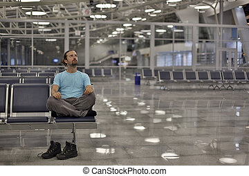 young man waiting his flight in airport lounge