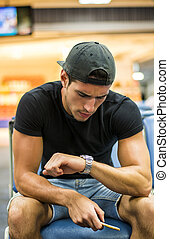 Young man waiting in sitting area at airport or station