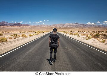 Young man walking alone through an empty street in the desert of
