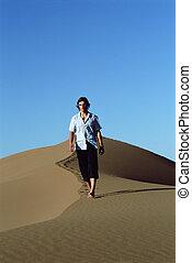 Young man walking along sand dune