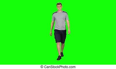 Young man walking on a Green Screen, Chroma Key. Guy in a gray T-shirt, shorts and sneakers walks at a slow pace, smiles and wonders