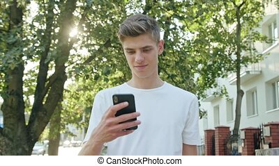 Young Man Walking and Using a Phone in Town - An attractive...