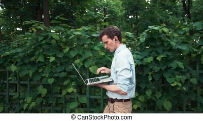 Young man walking at park using laptop with headphones and sit down on bench