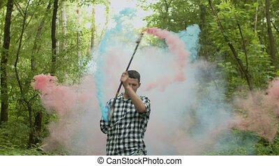 Young man walking in forest spinning smoking staff -...