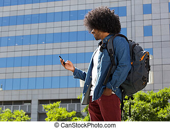 Young man walking in the city with cellphone