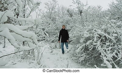 Young Man Walking in Winter Forest